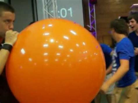 up a balloon with orange blowing up an orange balloon