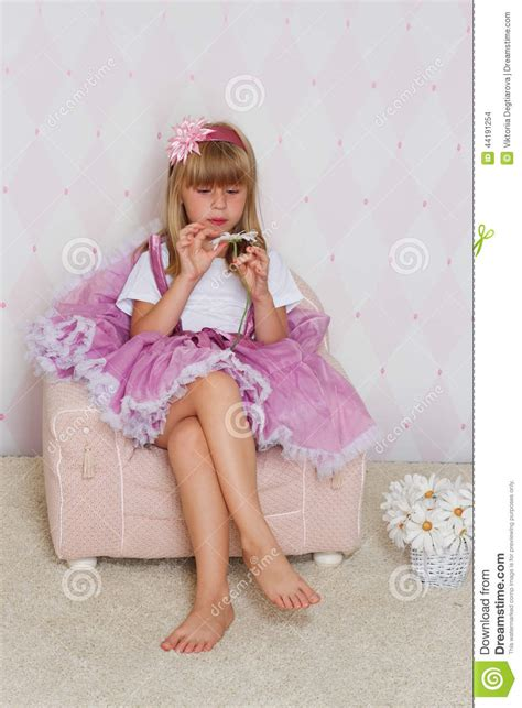 little girl on chair little girl is sitting on a chair stock photo image
