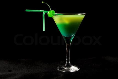 green cocktail black background green cocktail with cherry isolated on black stock photo