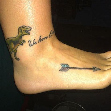 dinosaurio y flecha en pie tatuajesxd