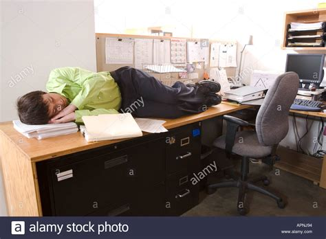 office worker at desk office worker asleep on desk stock photo royalty