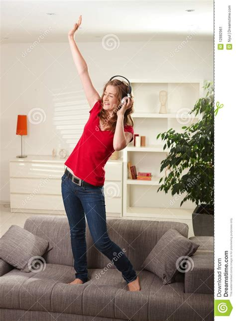 couch dance happy girl dancing on couch with headphones stock image