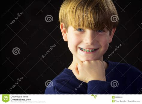 young boy shows   green braces royalty  stock  image