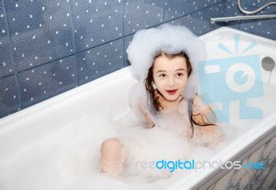 one girl one bathtub surprised little girl sitting in a bath with soap suds