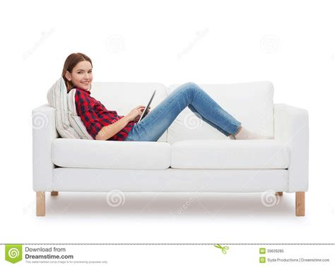 girl sitting on couch teenage girl sitting on sofa with tablet pc stock photo