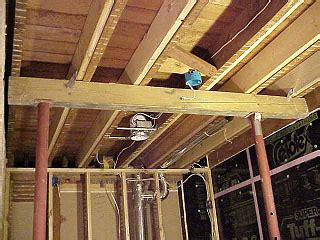 basement floor joists beam and lally columns used to lift sloping floor after