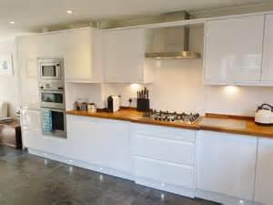 beautiful white gloss handleless kitchen with iroko wood