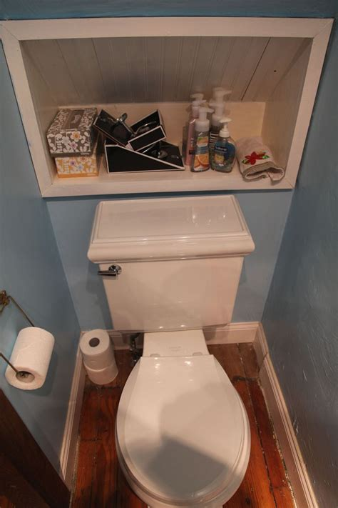 under bathroom shelf in wall behind toilet under stairs half bath