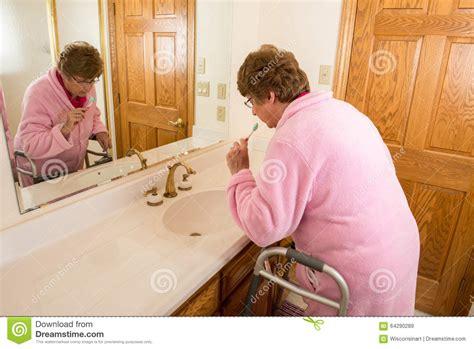 senior bathroom aids elderly senior woman brushing teeth stock photo image