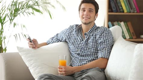 guy on the couch attractive guy sitting on couch drinking juice and smiling