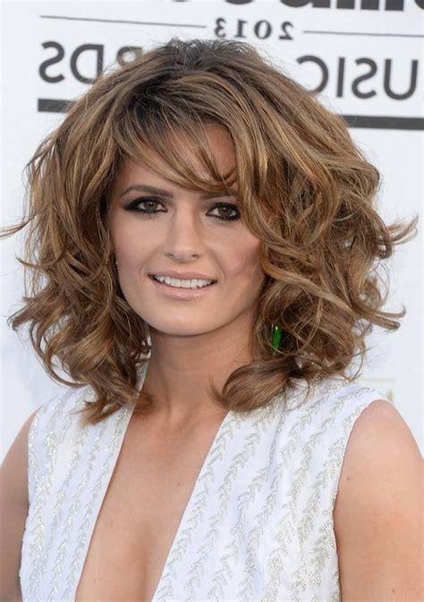 stana katic layered medium curly hairstyle  bangs