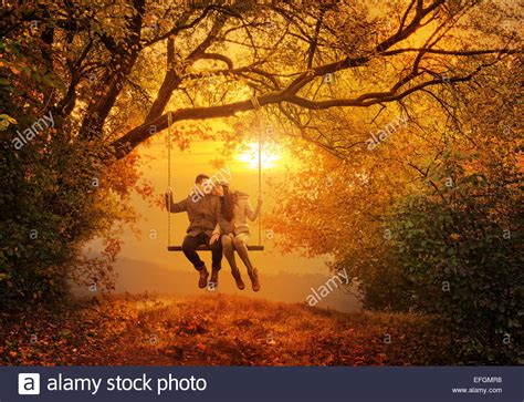 couples swing swing in the autumn park stock photo