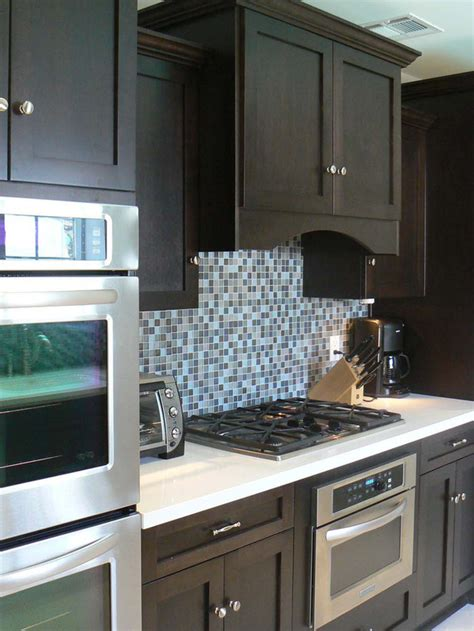 blue tile kitchen backsplash contemporary kitchen with rich brown cabinetry and mosaic