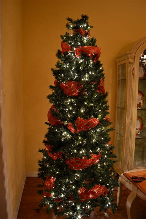 creations decorating a christmas tree with mesh ribbon