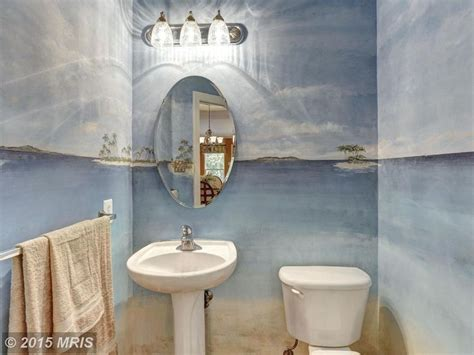 tropical powder room with howard elliott oval mirror moen