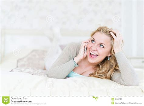 lying on the bed blonde lying on bed and phoning stock photo image 39939131