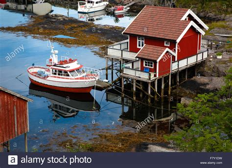 small boat with cabin brick red wooden cabin on stilts and small fishing boat