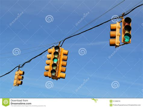 blue lights on traffic signals traffic lights in front of blue sky stock photo
