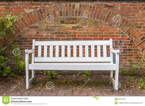 the front bench white bench in front of red brick wall chained to the