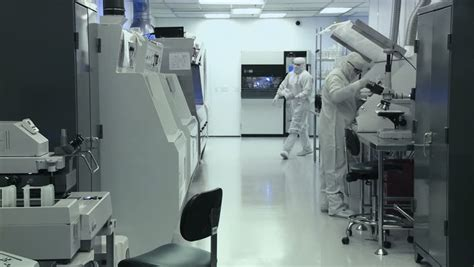 clean room bunny suit scientists and technicians working on silicon chip manufacture in a clean room wearing