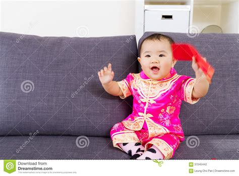 Asian baby holding red pocket with traditional chinese clothing stock photo image of giggle