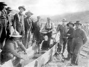 Miners standing around sluice two men panning for gold c 1898