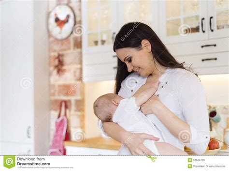 baby swings arm while nursing mother breastfeeding her baby stock photo image 51524779