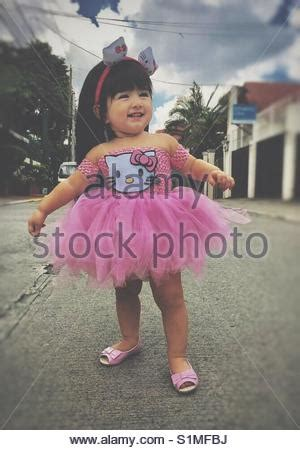 Mini Dress Anak Hello Pink wearing dress and shoes is lying on comfortable chair stock photo royalty free
