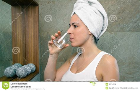 drinking water from bathroom young woman drinking glass of water in bath stock photo