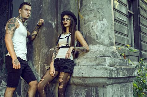 old tattooed couple stylish tattooed in black shorts standing at