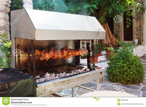 backyard rotisserie outdoor grill with meat in naxos island greece stock