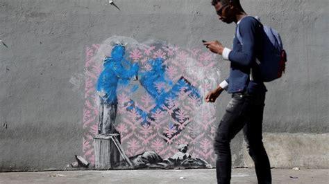 banksy strikes  murals  famed graffiti artist