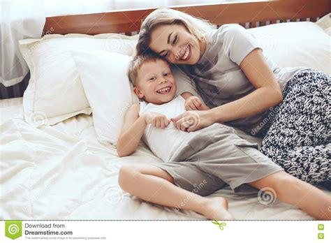 mother and son bedroom scene mother plays with son in bed stock photo image 70399722