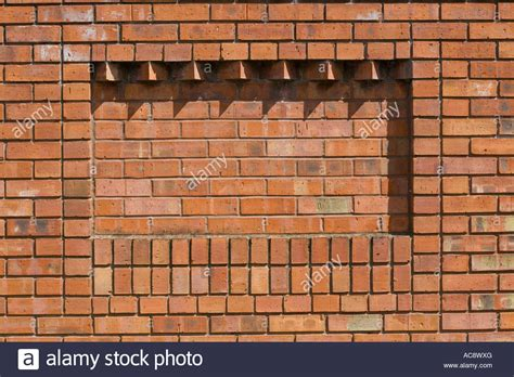 brick pattern wall covering corbelling in brickwork providing relief pattern on red