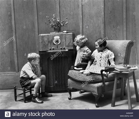 living room radio 1930s two and a boy sitting in living room listening to stock photo royalty free