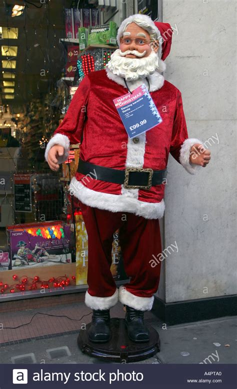 a musical santa claus outside an electronics shop london