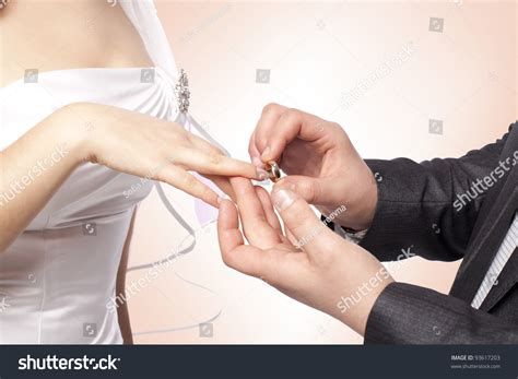 stock photo hands with rings groom putting golden ring on