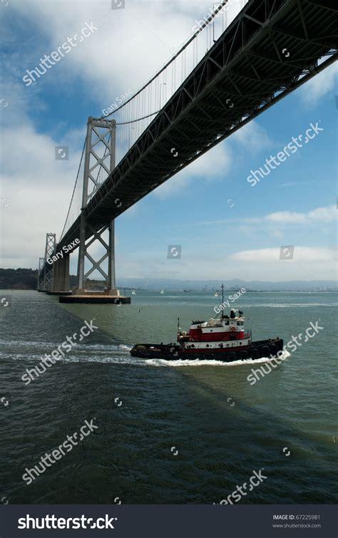 boats under san francisco tug boat passing under the san francisco bay bridge stock