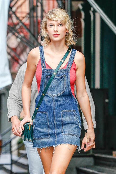 wears a denim overalls dress the