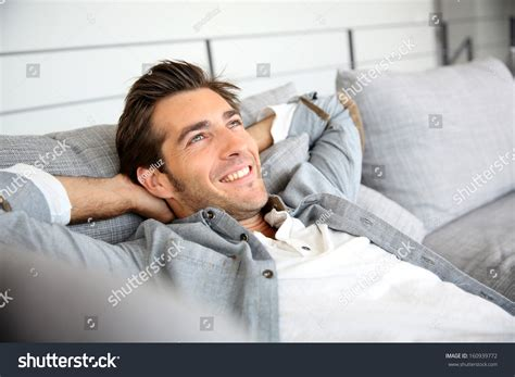 little girl behind the couch song man relaxing in sofa with arms behind head stock photo