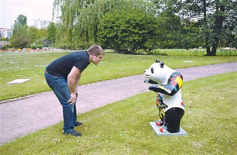 a visitor checks out at a panda sculpture iat gardens of