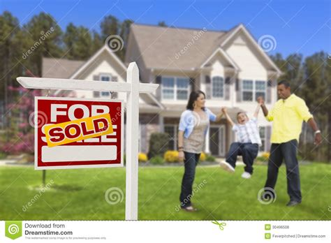 hispanic family in front of sold real estate sign house