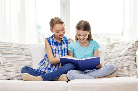two girls having on couch two happy girls reading book at home stock image image