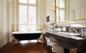 Vintage bathroom design with clawfoot bathtub and large wall mirror in