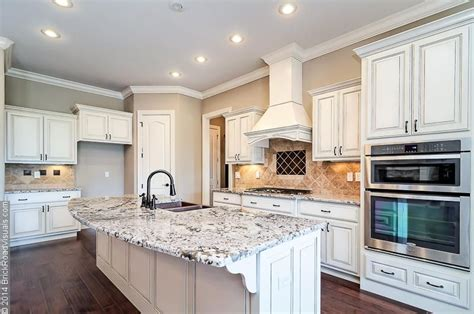 bianco antico granite with white cabinets open floor plan featuring antiqued white kitchen cabinets