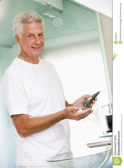 men in bathroom man in bathroom applying aftershave royalty free stock