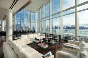 Dark wood flooring sofas floor to ceiling windows city amp river