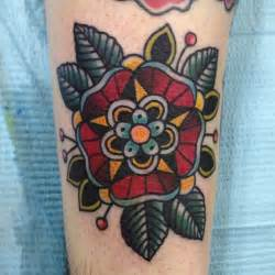 red flower and green leaves traditional tattoo