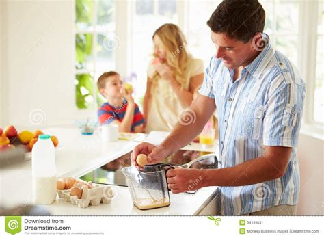 family in kitchen father preparing family breakfast in kitchen stock image