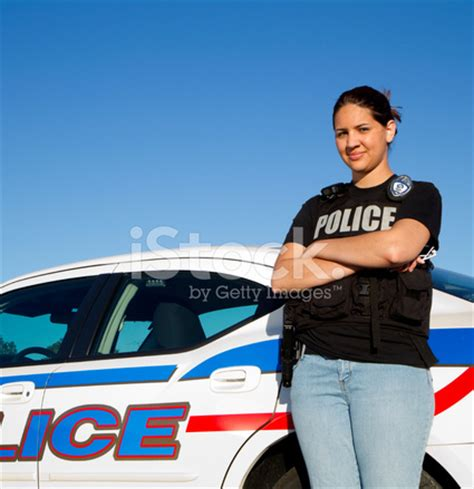 hispanic police woman standing against car stock photos